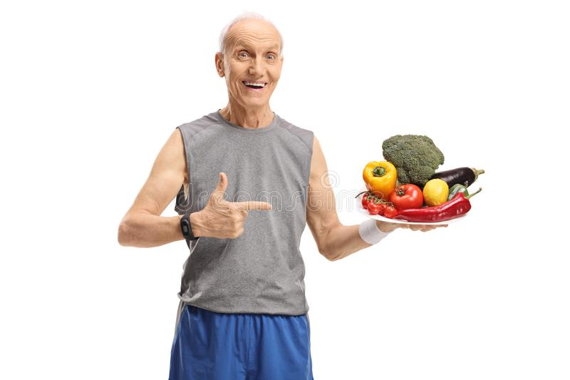 Lyckligt högt innehav som en platta fyllde med frukt och grönsaker royaltyfri foto