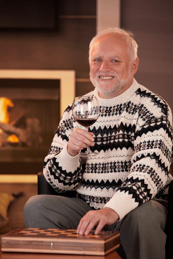 lyckligt ha wine för manståendepensionär arkivfoto