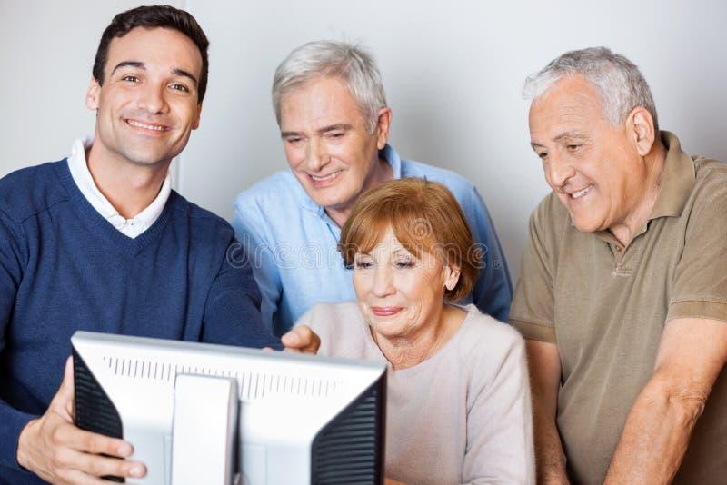 Lyckligt handleda Assisting Senior People, i att använda datoren på grupp arkivbilder