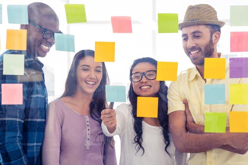 Lyckligt idérikt folk som diskuterar över självhäftande anmärkningar arkivfoto