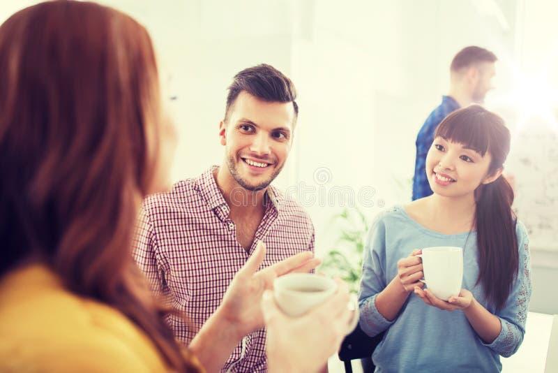 Lyckligt idérikt lag som dricker kaffe på kontoret royaltyfri fotografi