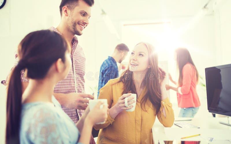 Lyckligt idérikt lag som dricker kaffe på kontoret arkivbilder