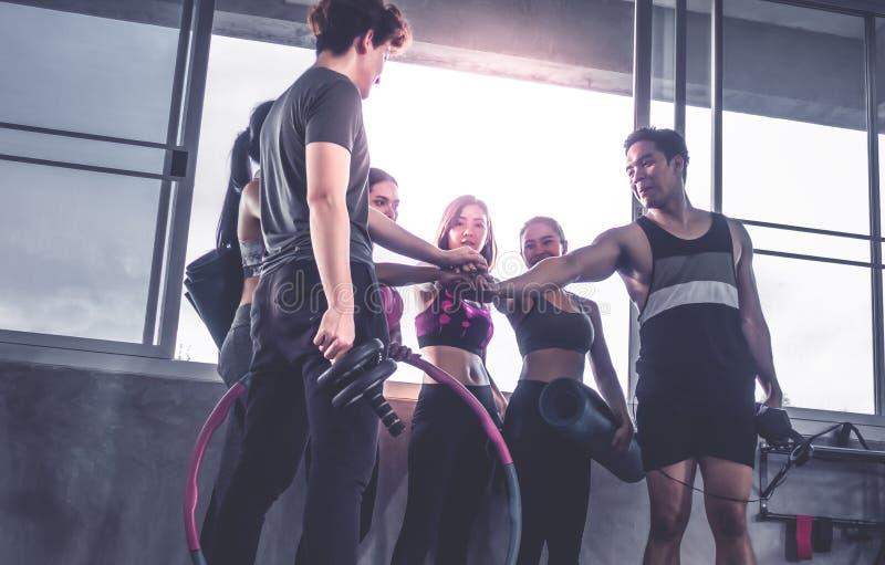 Lyckligt idrotts- folk i sportswearen som tillsammans sätter handen i idrottshallen royaltyfria bilder