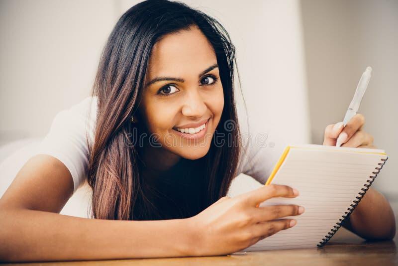 Lyckligt indiskt studera för handstil för utbildning för kvinnastudent fotografering för bildbyråer