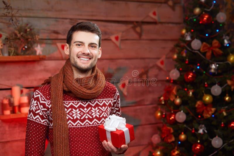 Lyckligt innehav för ung man som är närvarande i jultid arkivfoto