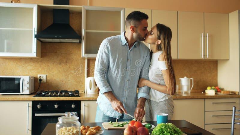 lyckligt kökbarn för par Det stiliga manmötet och kysser hans flickvänotta arkivfoton