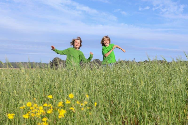 Lyckligt köra för ungar som spelar, utomhus royaltyfri foto