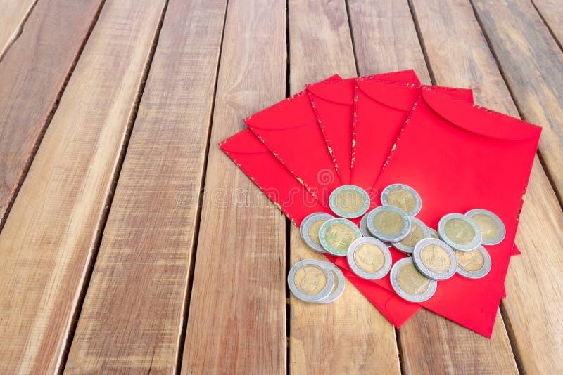 Lyckligt kinesiskt nytt år, rött kuvert eller kallade Angpao och guld- mynt på träbakgrund royaltyfri bild