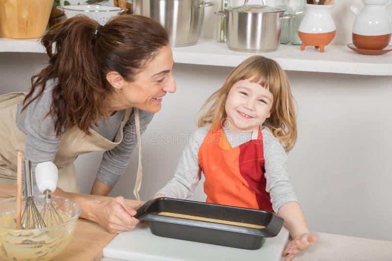 Lyckligt klart för barn och för moder till att baka kakan royaltyfria foton