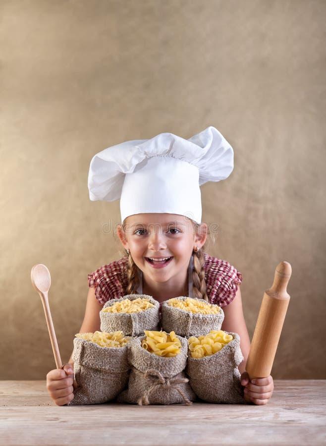 Lyckligt kockbarn med pastasortimentet royaltyfria foton