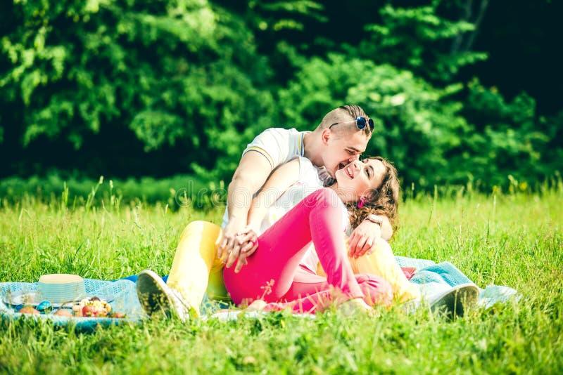 Lyckligt koppla av för par som är utomhus- i gräsplanen, parkerar royaltyfri fotografi