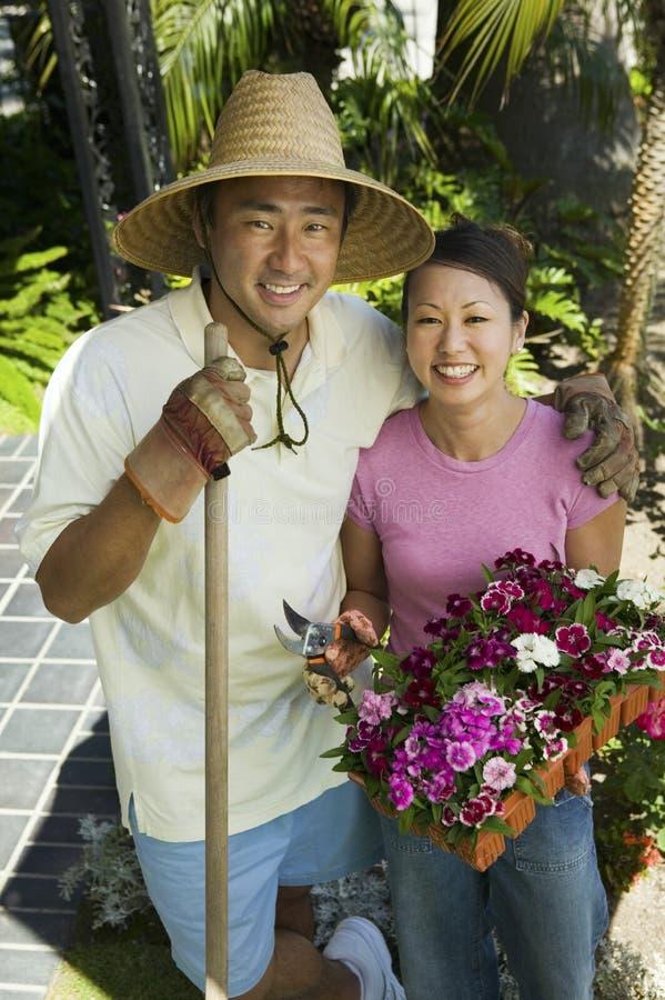 Lyckligt koppla ihop att arbeta i trädgården tillsammans arkivfoton
