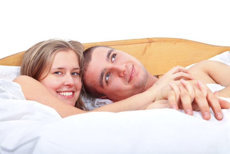 Lyckligt koppla ihop i säng arkivfoto