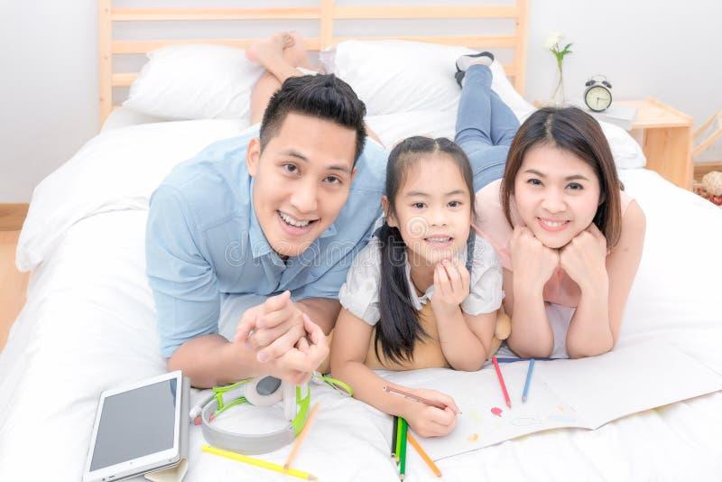 Lyckligt kopplar av le för asiatisk familj och på säng hemma royaltyfri fotografi