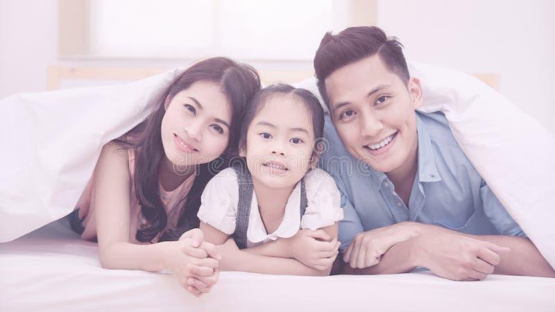 Lyckligt kopplar av le för asiatisk familj och på säng hemma arkivfoton
