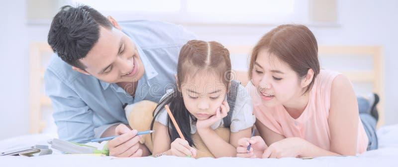 Lyckligt kopplar av le för asiatisk familj och på säng hemma royaltyfria bilder