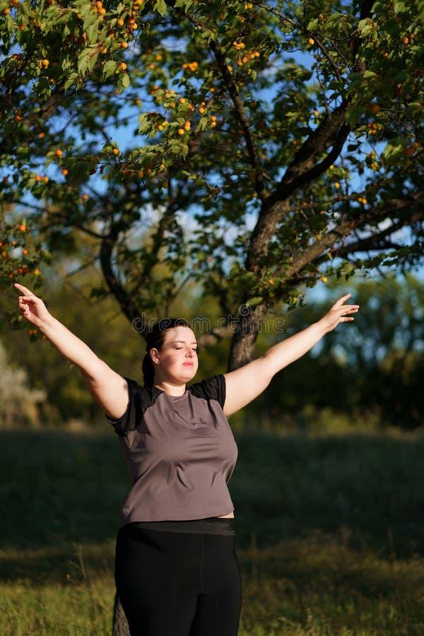 Lyckligt kvinnaanseende i natur med öppna händer royaltyfri foto