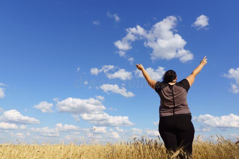 Lyckligt kvinnaanseende i natur med öppna händer arkivfoton