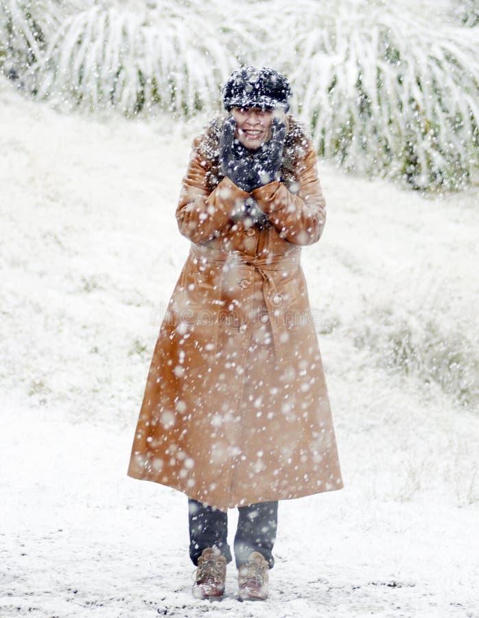 Lyckligt kvinnaanseende i ny fallande vit snö arkivfoton