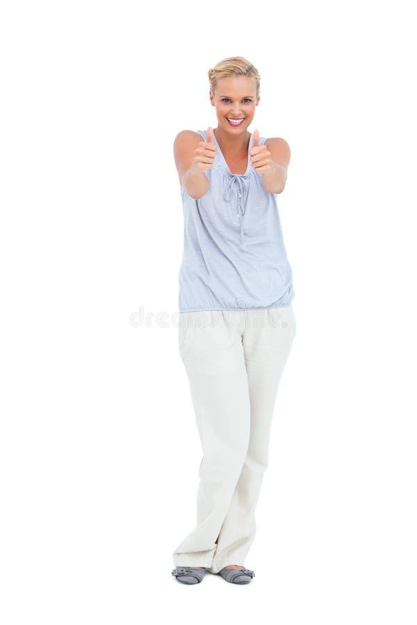 Lyckligt kvinnaanseende med tummar som ler upp på kameran fotografering för bildbyråer