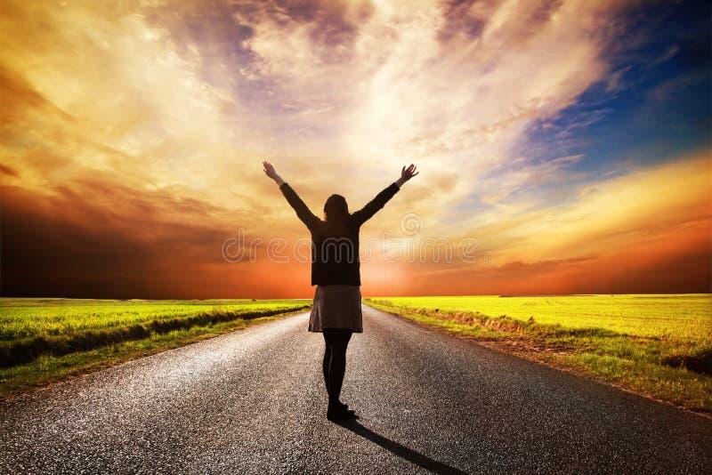 Lyckligt kvinnaanseende på den långa vägen på solnedgången royaltyfria foton