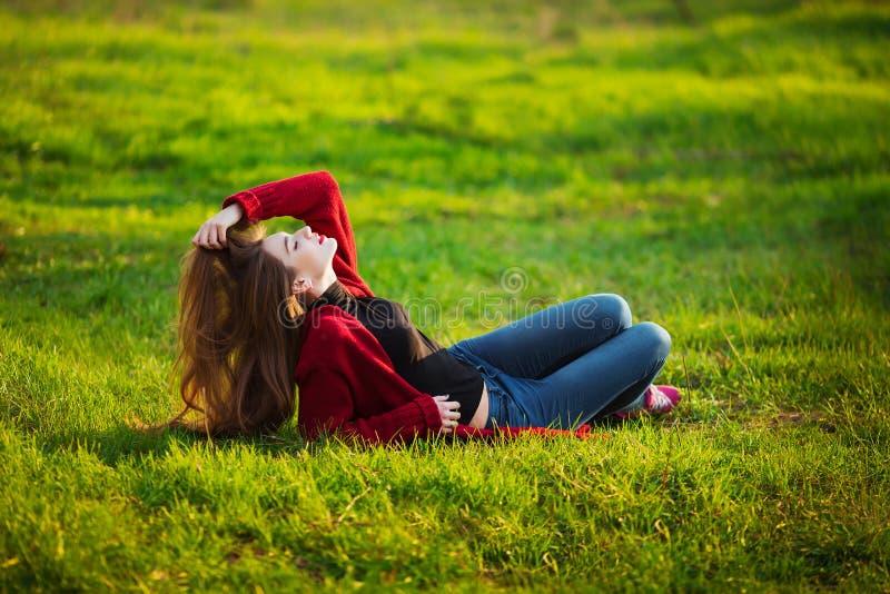 lyckligt kvinnabarn Den härliga kvinnlign med långt sunt hår som tycker om solljus parkerar in, sammanträde på grönt gräs Vår royaltyfria foton