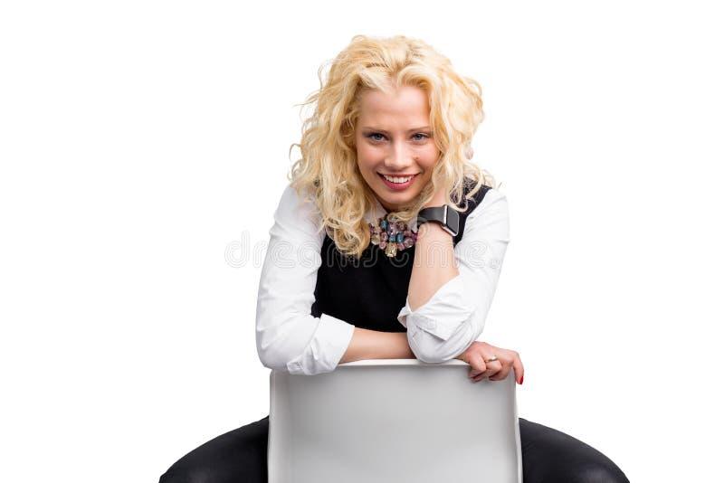 Lyckligt kvinnasammanträde i stol royaltyfri fotografi