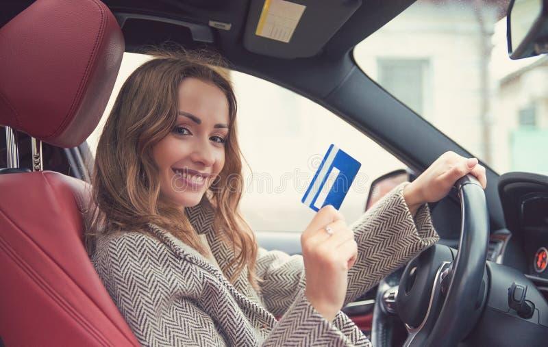Lyckligt kvinnasammanträde inom hennes nya kreditkort för bilvisning arkivfoto