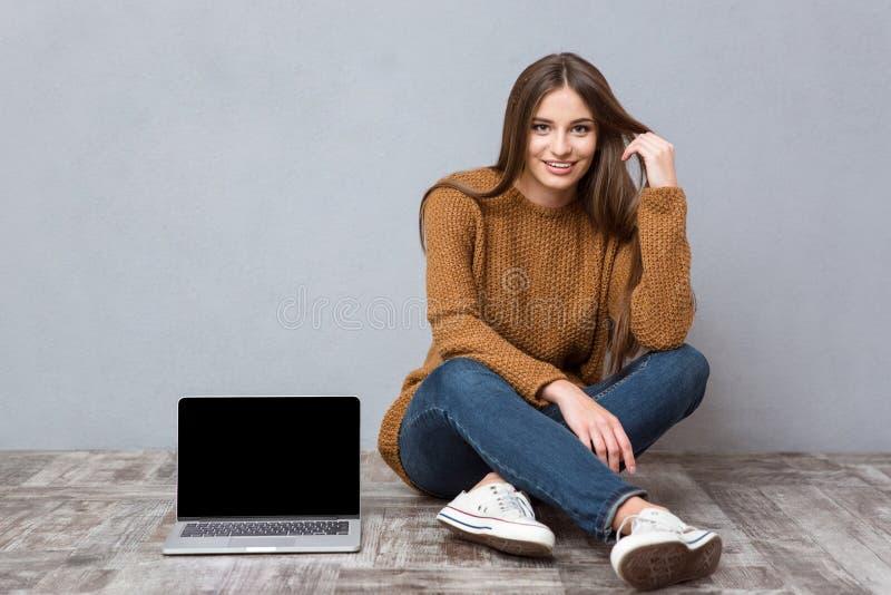 Lyckligt kvinnasammanträde på golv nära bärbara datorn med den tomma skärmen royaltyfri bild