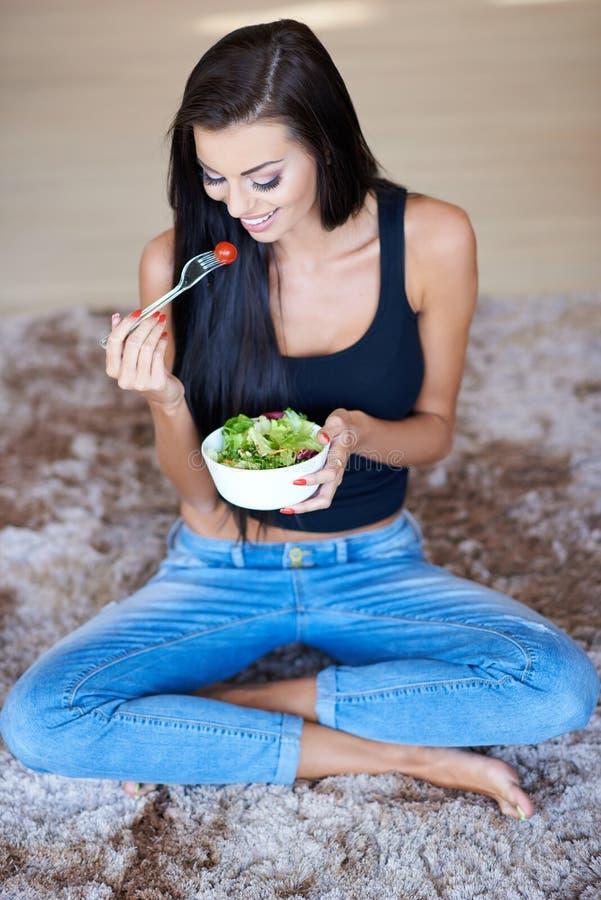 Lyckligt kvinnasammanträde på golvet som äter ny sallad arkivfoto