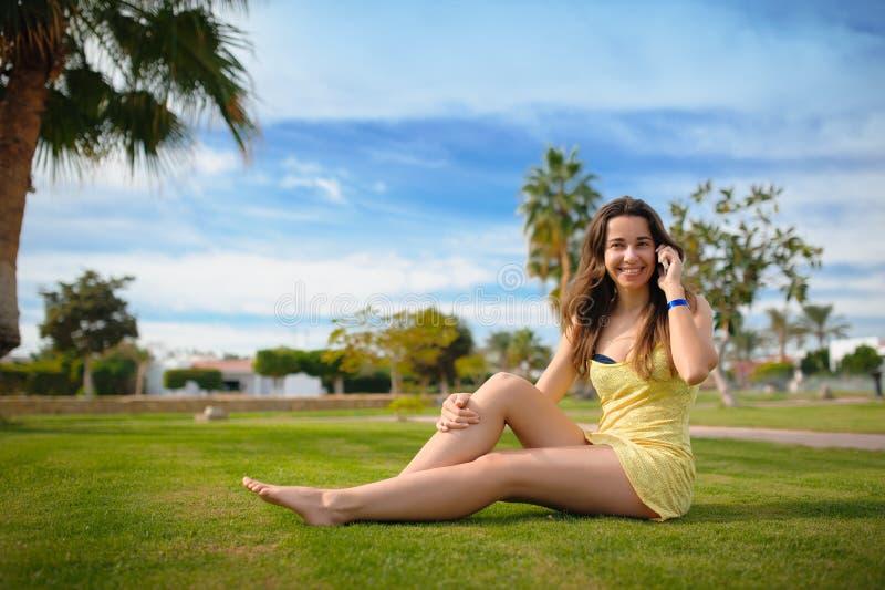Lyckligt kvinnasammanträde på gräset och samtal på telefonen royaltyfri fotografi