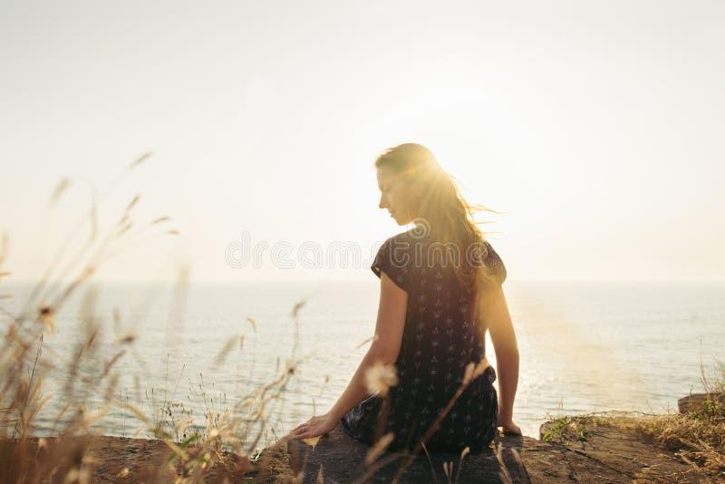 Lyckligt kvinnasammanträde på klippan på solnedgångbakgrund arkivbilder