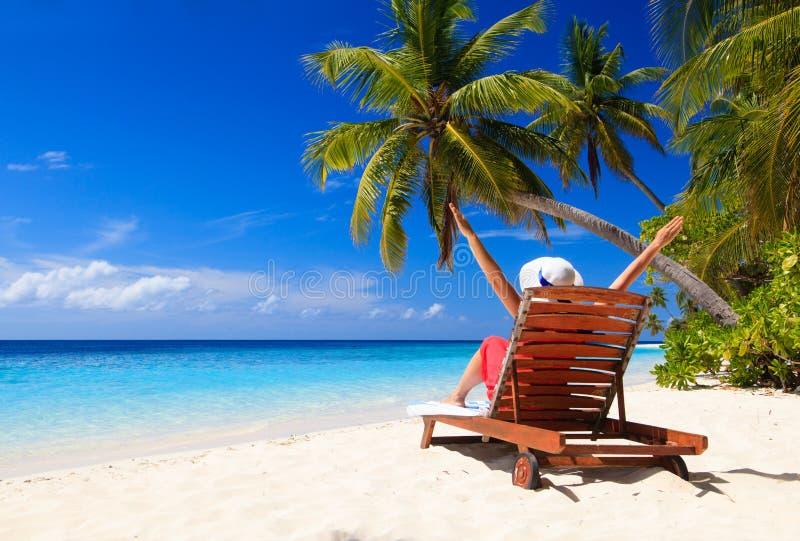 Lyckligt kvinnasammanträde på strandstol på tropiskt arkivfoton