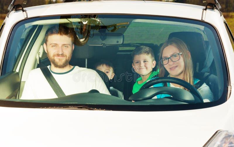 Lyckligt kvinnligt chaufförsammanträde i bil med hennes familj arkivfoton
