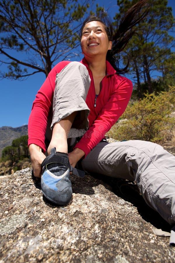 Lyckligt kvinnligt fotvandraresammanträde på de bärande skorna för vagga som förbereder sig för, vaggar klättring arkivfoton