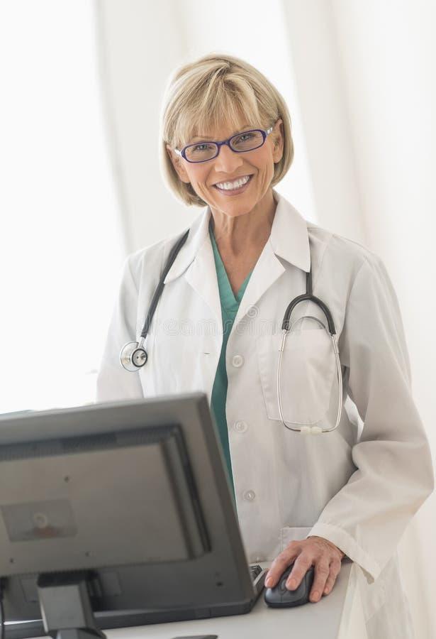 Lyckligt kvinnligt skrivbord för doktor Using Computer At arkivbilder