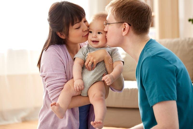 Lyckligt kyssa för moder och för fader behandla som ett barn sonen hemma royaltyfri bild