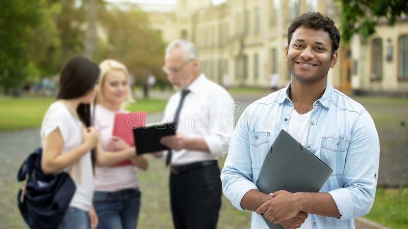 Lyckligt latinamerikanskt studentanseende nära högskolan och le på kameran, utbildning arkivbild