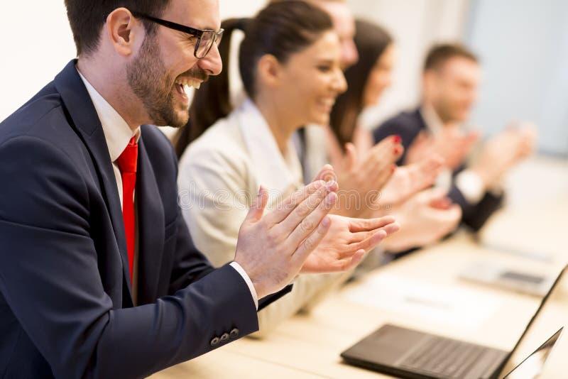 Lyckligt le affärslag som applåderar händer under ett möte arkivfoton