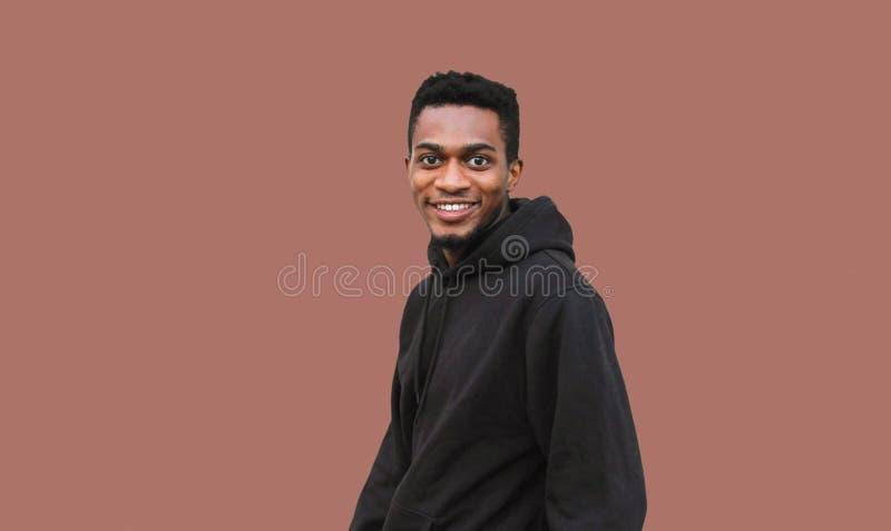 Lyckligt le afrikanskt mananseende för stående i den svarta hoodien som isoleras på brunt arkivfoton