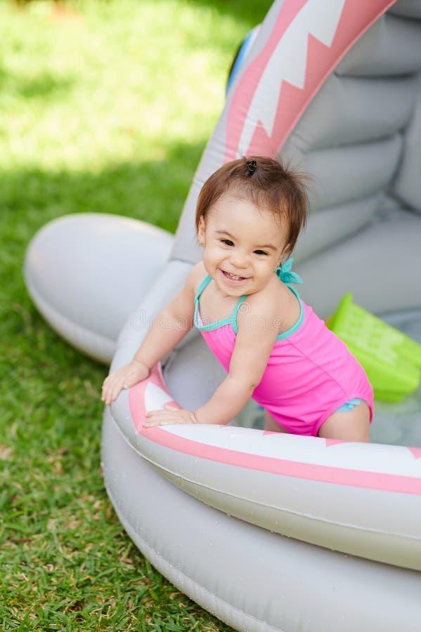 Lyckligt le behandla som ett barn flickastaget i simbassäng arkivfoton