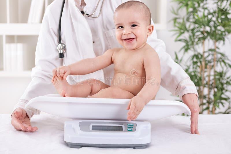 Lyckligt le behandla som ett barn i det pedrician kontoret som mäter vikt arkivfoton