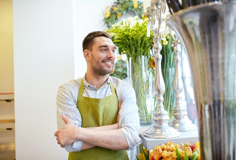 Lyckligt le blomsterhandlaremananseende på blomsterhandeln arkivbilder