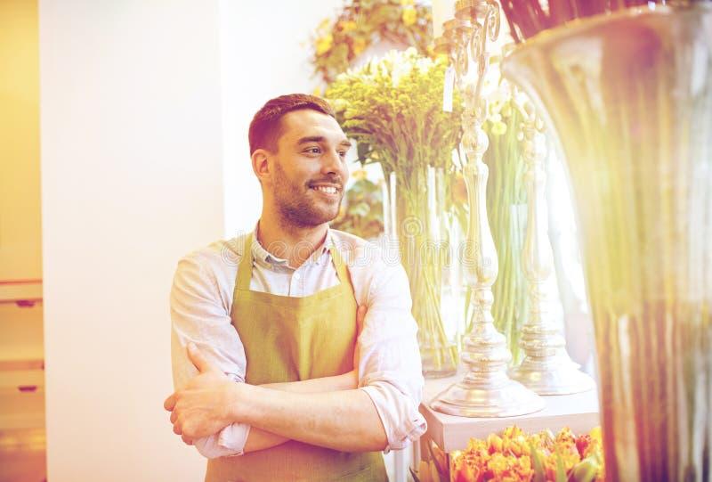 Lyckligt le blomsterhandlaremananseende på blomsterhandeln royaltyfri bild