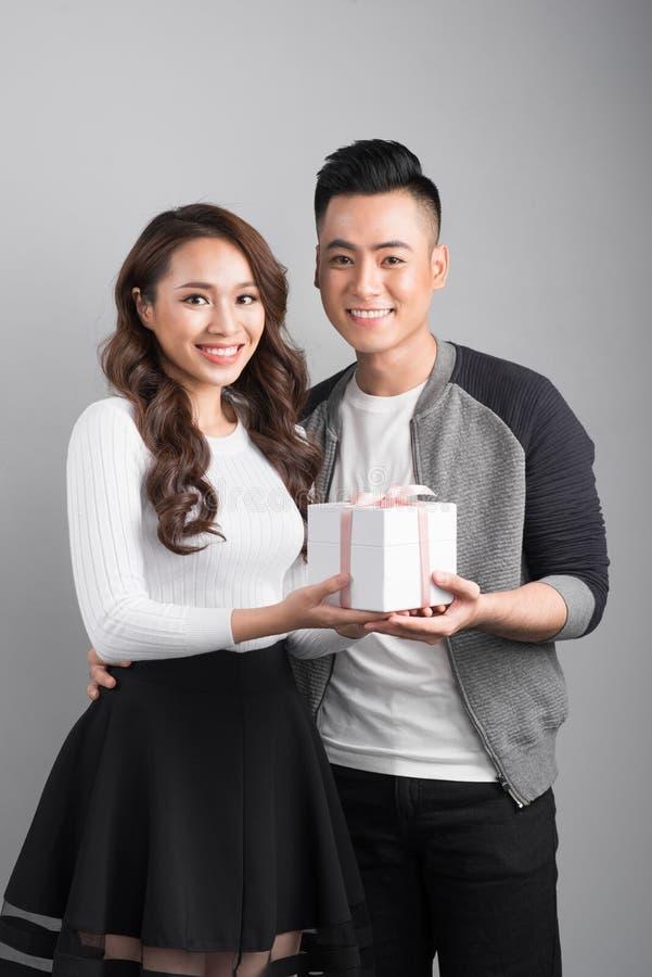 Lyckligt le förälskat anseende för par över grå bakgrund arkivfoton