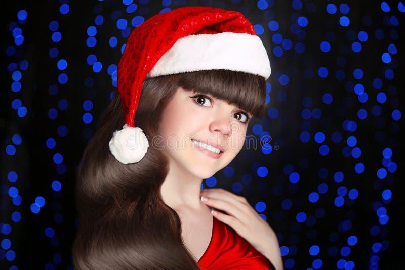 Lyckligt le för den santa tonårigt flickan bär i röd hatt med vit päls po arkivbild
