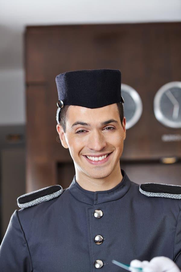 Lyckligt le för hotellportvakt arkivbild