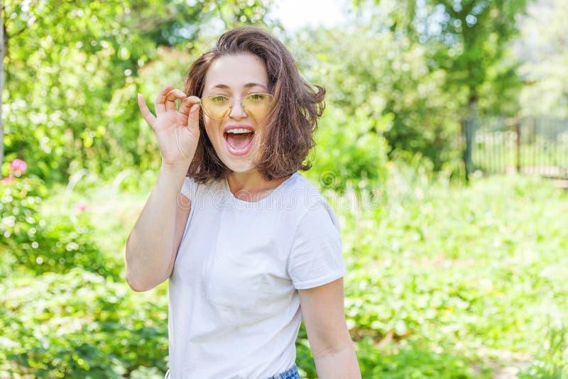 lyckligt le f?r flicka Kvinnan för brunetten för skönhetståenden parkerar den unga lyckliga positiva skratta i moderiktig gul sol fotografering för bildbyråer