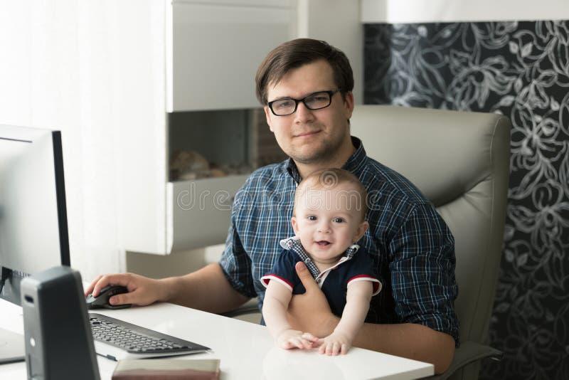 Lyckligt le fadersammanträde med hans lilla son och arbete på royaltyfri bild