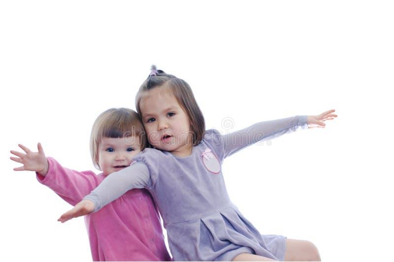 Lyckligt le flyga för två små flickor som isoleras på vit bakgrund sibling med olikt spela för ålder royaltyfria foton